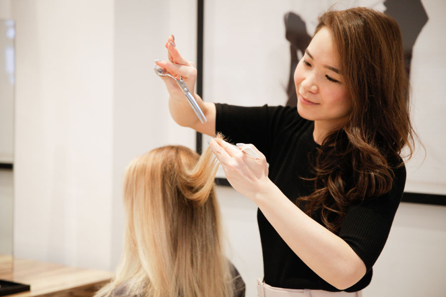 Japanese Hairstylist and Artistic Director Yoko, cutting a client's hair.